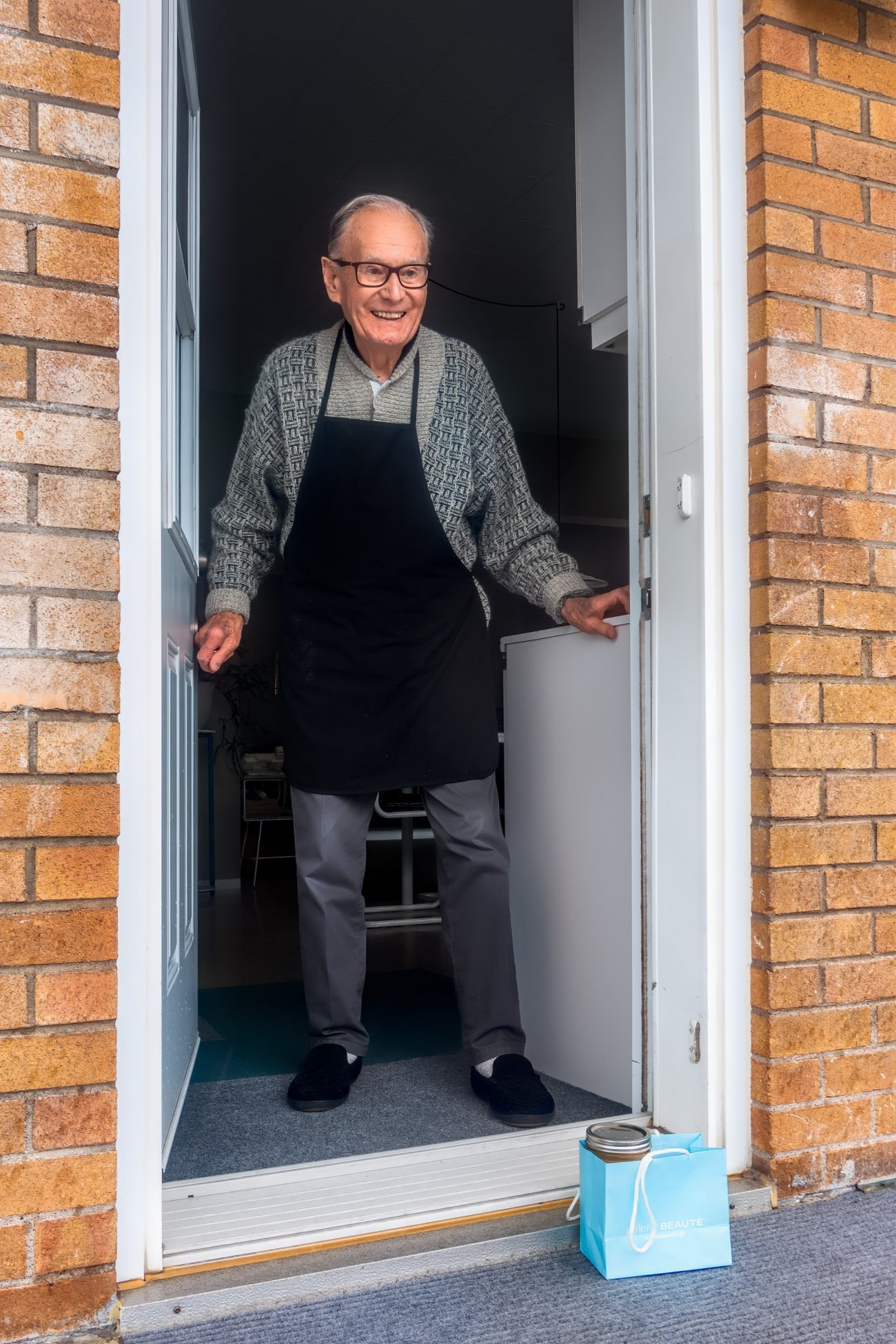 Grandfather is greeted at front door with a gift.