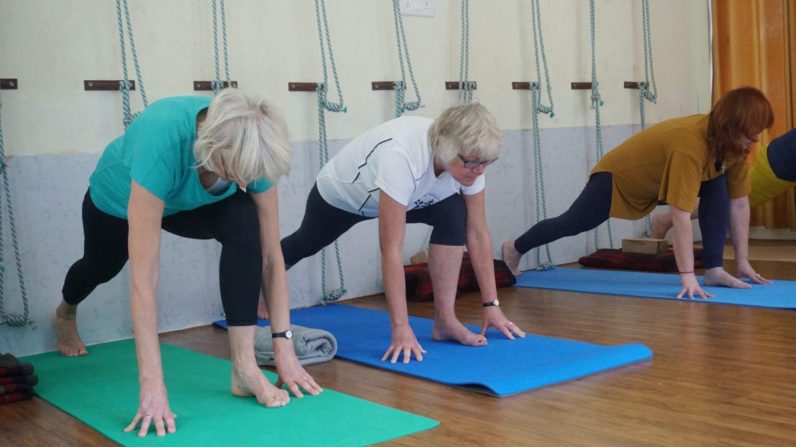 Two older women doing a yoga class.