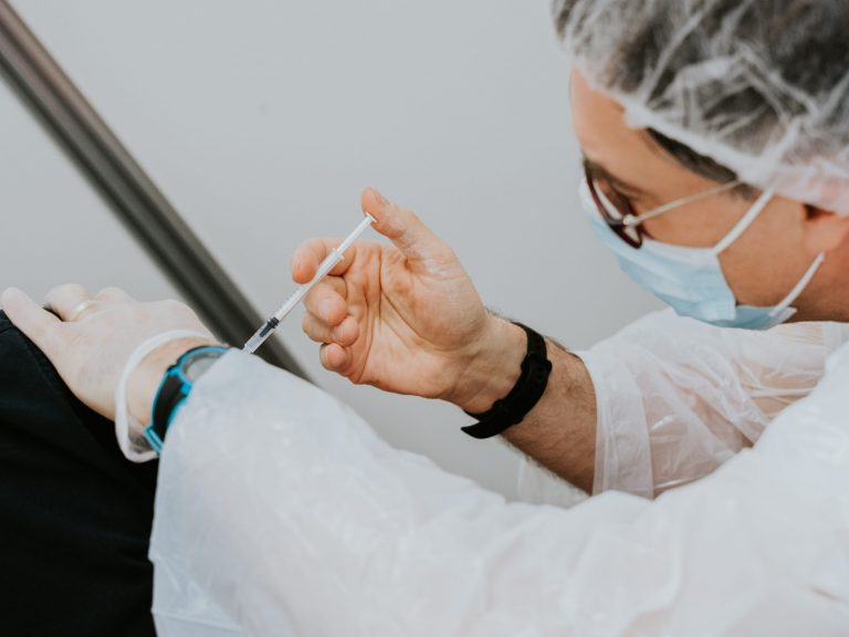 Clinical professional provides vaccination to a patient's arm.