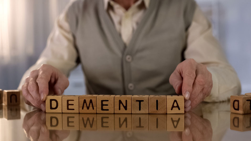an elderly person spelling out dementia with wood blocks