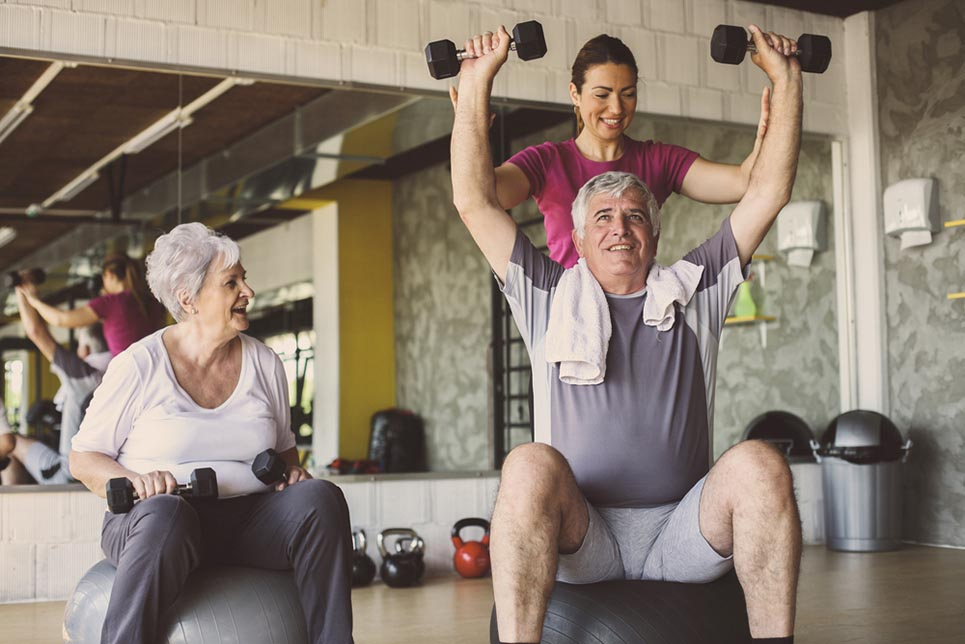 a senior couple exercising with dumbbells