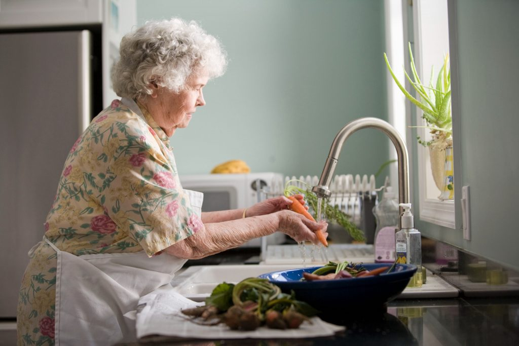 Older women at the sink washing vegetables.