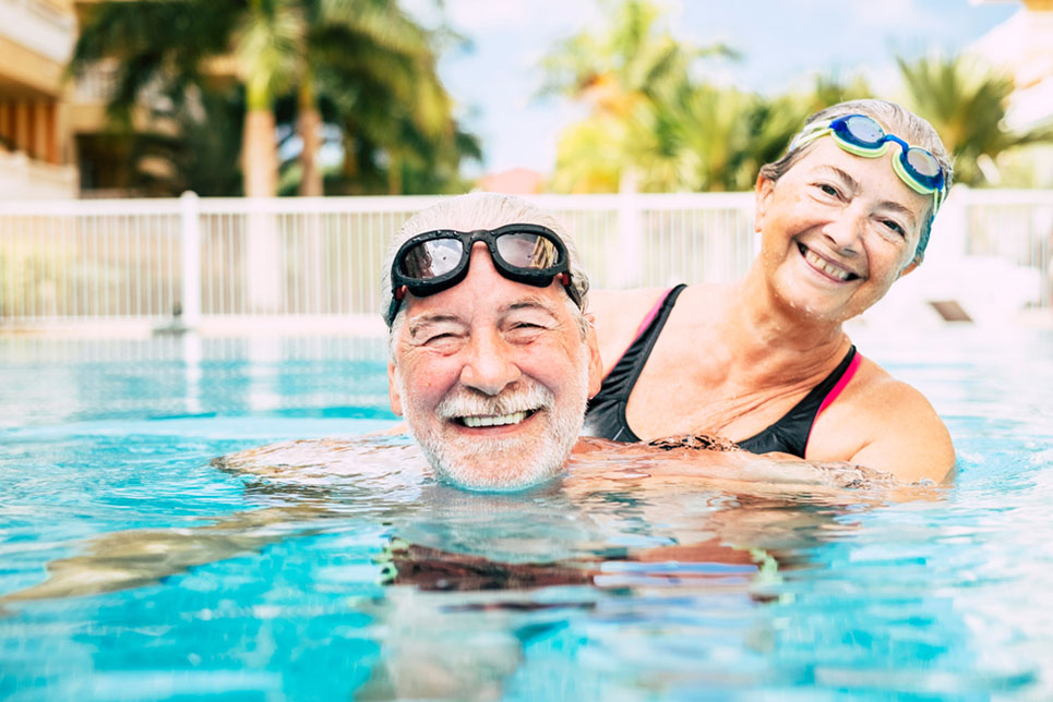 happy older couple exercise in pool