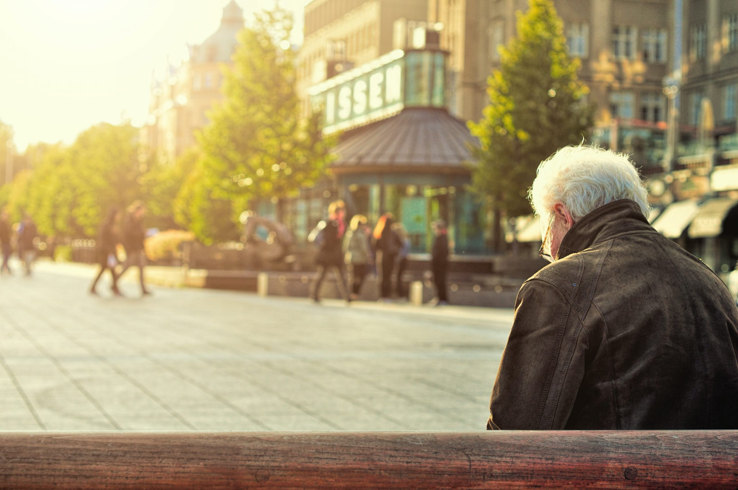 Older man sitting on a bench in a city. Looking downwards. People walking by at a distance.