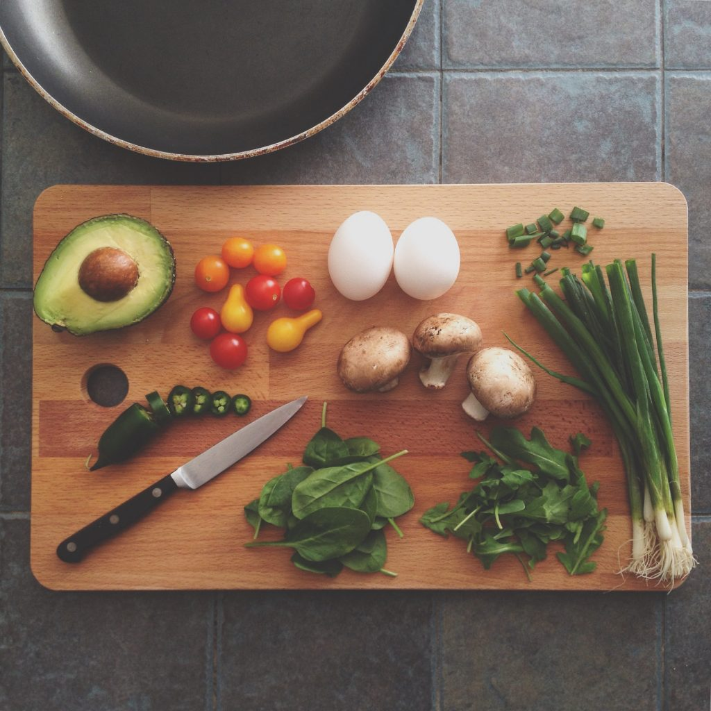 Wooden cutting board with a knife preparing to chop a variety of healthy foods. Including vegetables and hard boiled eggs.