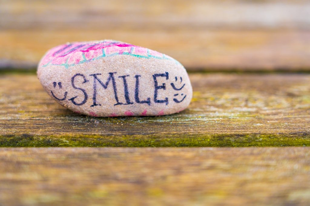 A rock with the word smile on it, surrounded by smileys, to keep spirits up during the COVID pandemic and lockdown.