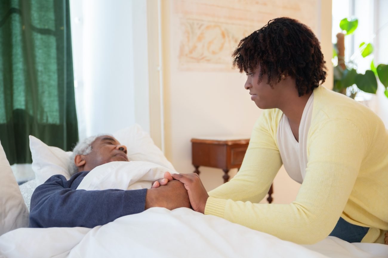 Young women sitting beside bed and holding hand of older man laying down.
