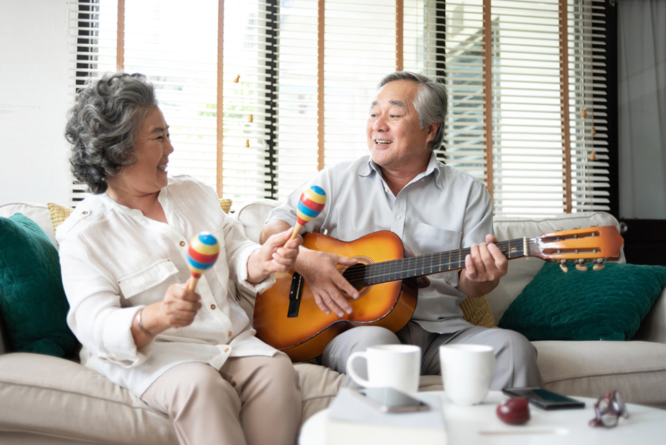 Asian senior Couple singing and playing acoustic guitar together. Elderly man, woman having fun with String instrument. Older people enjoying while sitting in couch at house. life, Lifestyle, Carefree