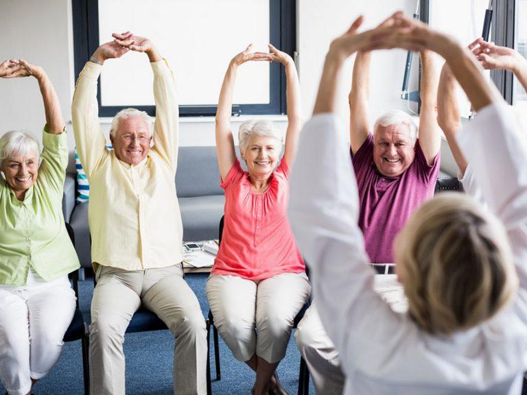 sitting seniors stretching arms upward