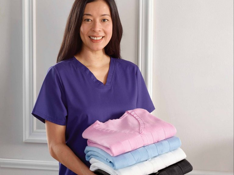Care worker holding 4 folded cardigans