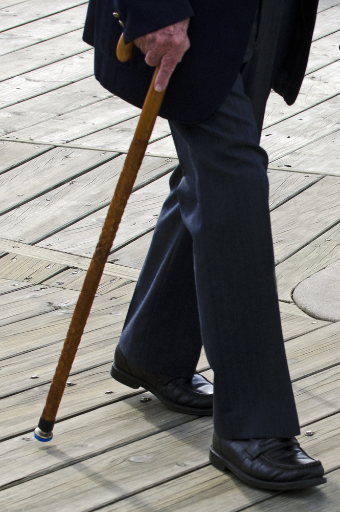 an elderly person walking with a cane