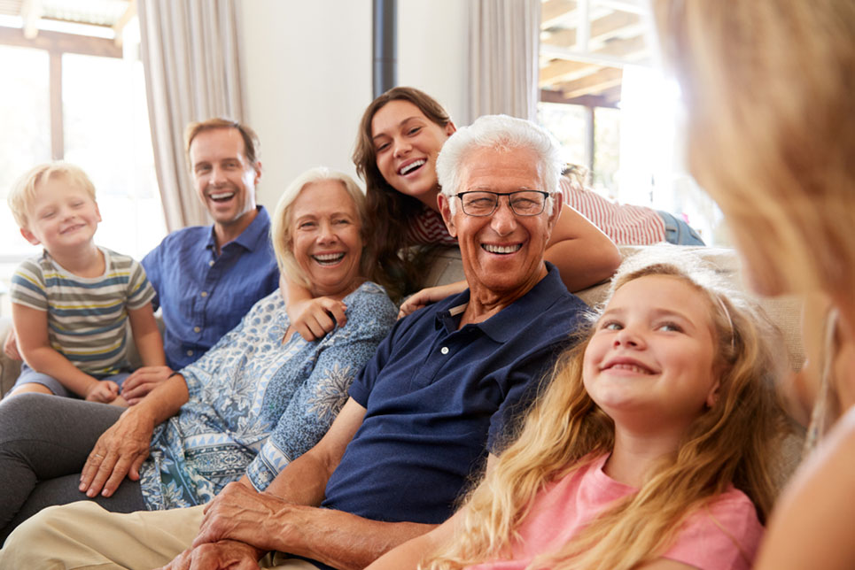 Multi-Generation Family Sitting On Sofa