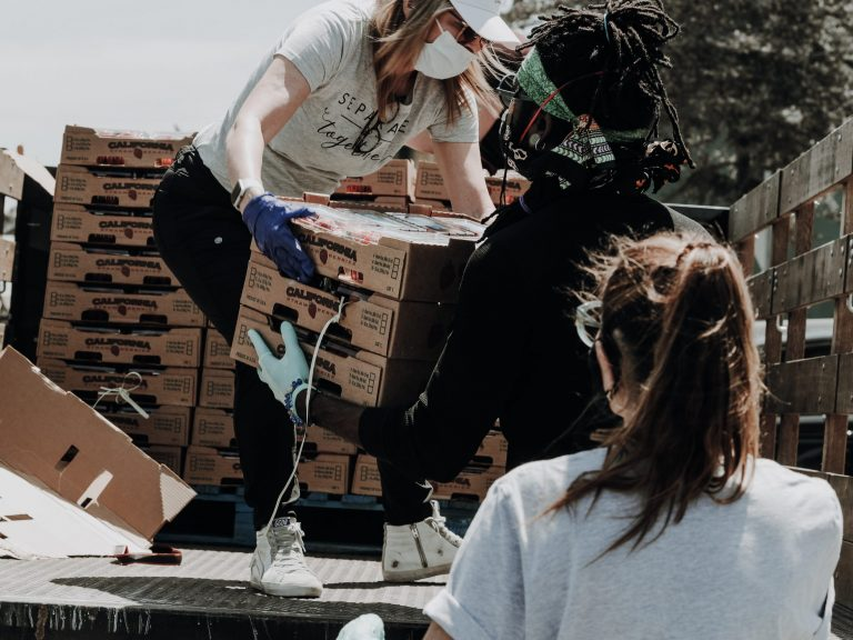 Woman passing boxes of food off a truck to young man.