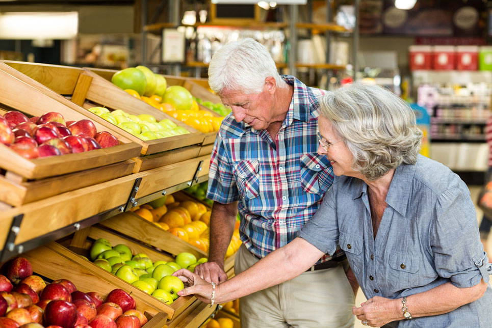 a senior couple buying apples