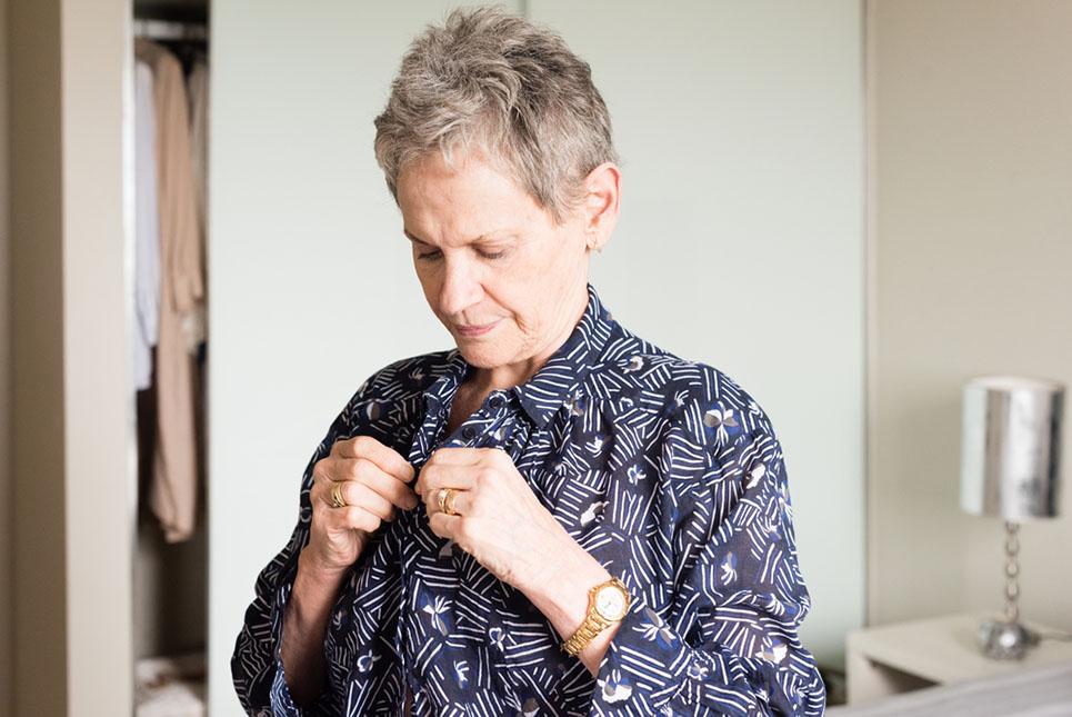 an older woman buttoning her shirt